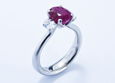 Four claw three stone platinum ring with ruby and diamonds