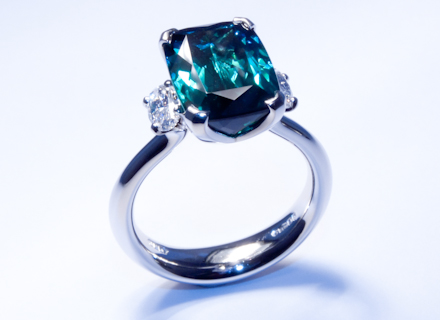 Four claw three stone platinum ring with a cushion cut indicolite tourmaline and oval diamonds