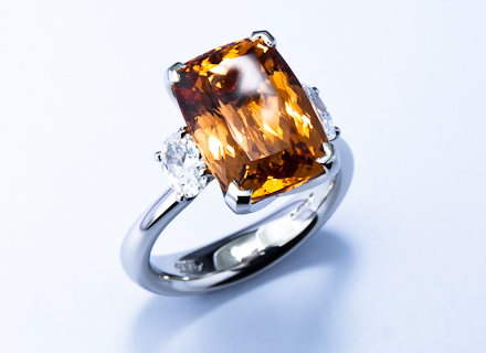 Four claw three stone platinum ring with an Imperial topaz and oval diamonds