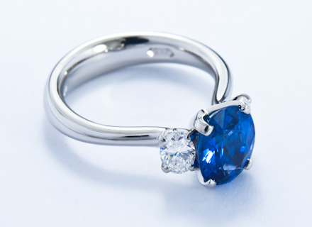 Four claw three stone platinum ring with an oval blue sapphire and diamonds