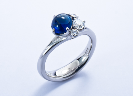 Meadow cross over cluster platinum ring with cabochon blue sapphire and diamonds
