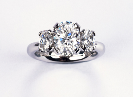 Four claw three stone platinum ring with oval brilliant cut diamonds